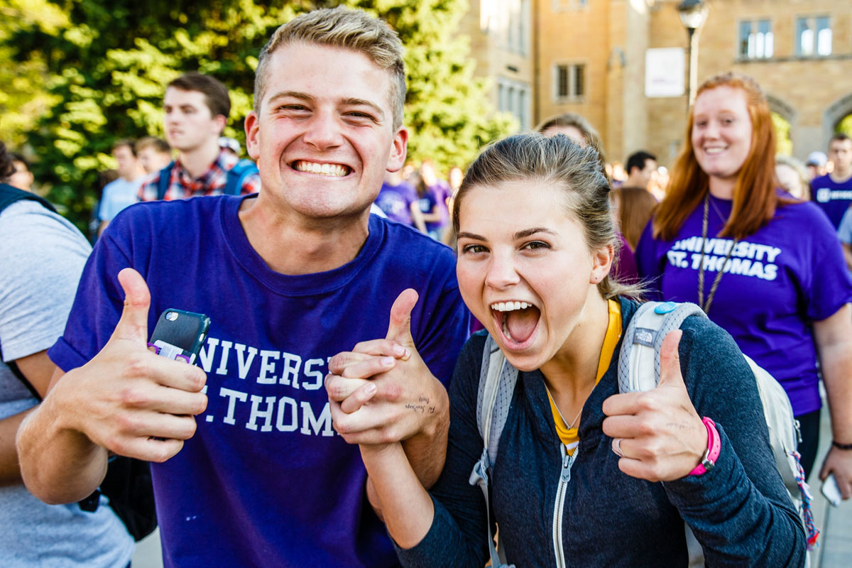 Students give a thumbs up after marching through the arches.