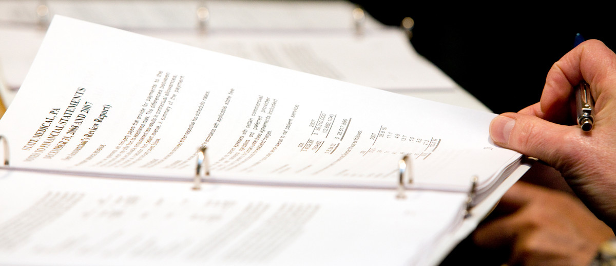 a person pages through financial statements