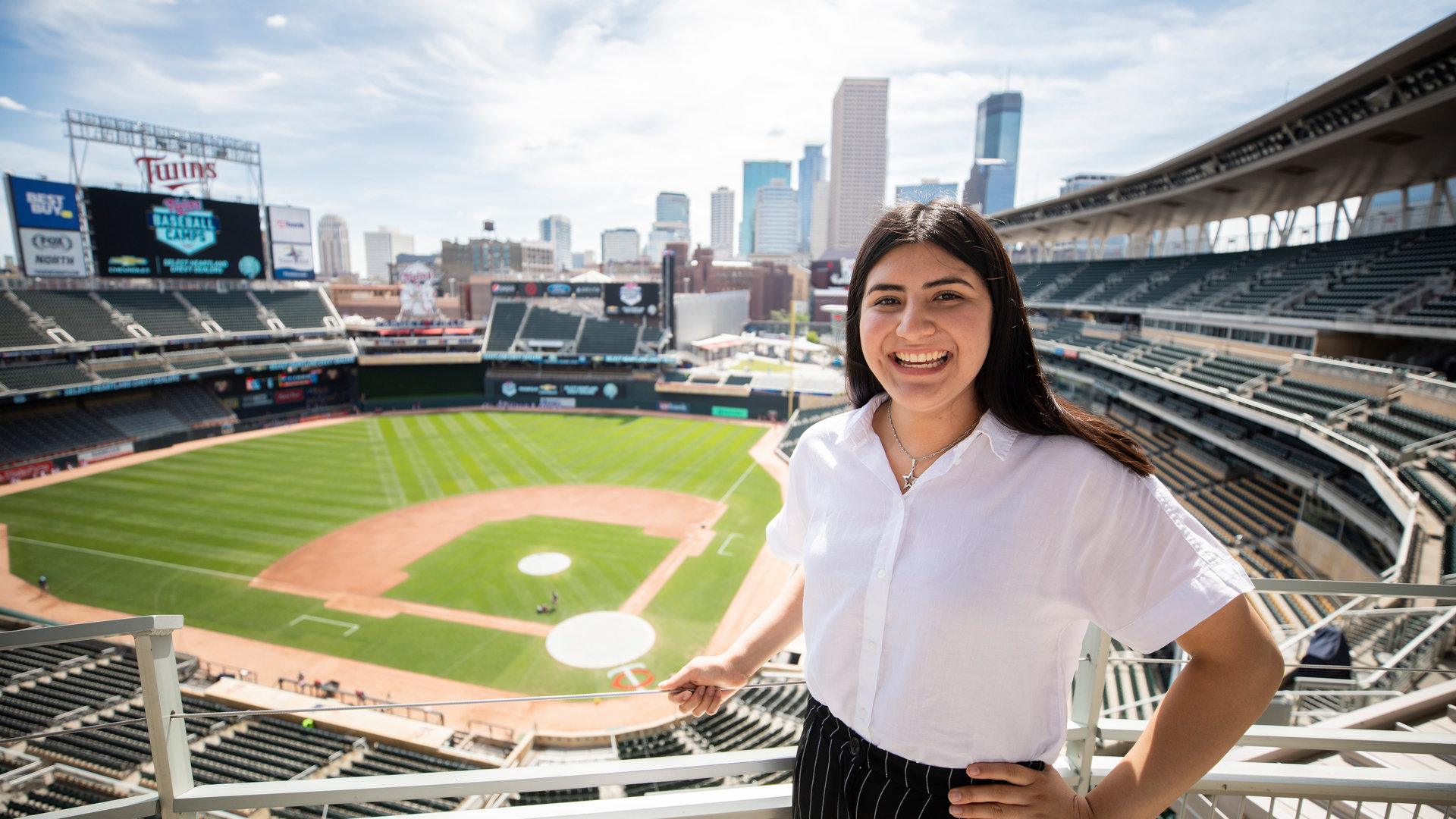 dfc student stands in the Twins stadium, the venue for her corporate internship