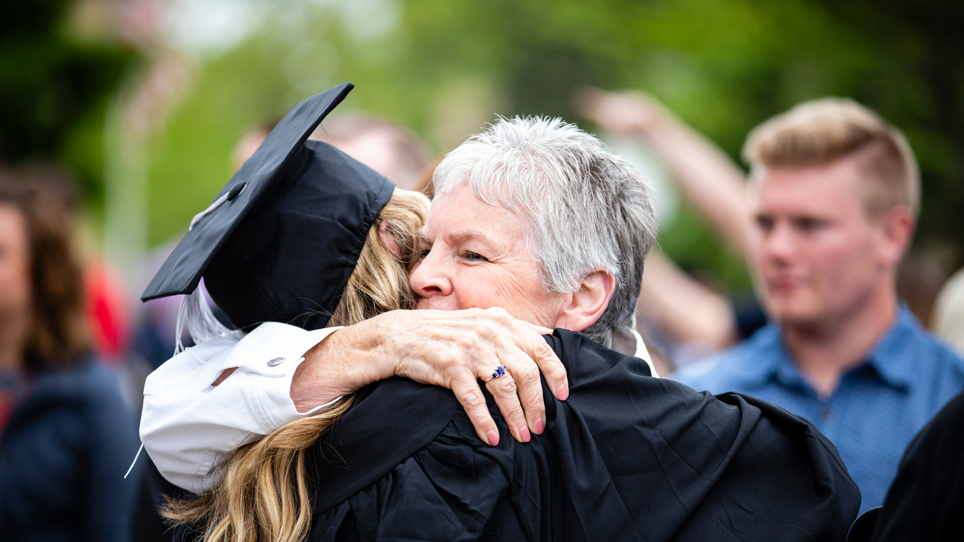 a woman with grey hair hugs a graduate at commencement