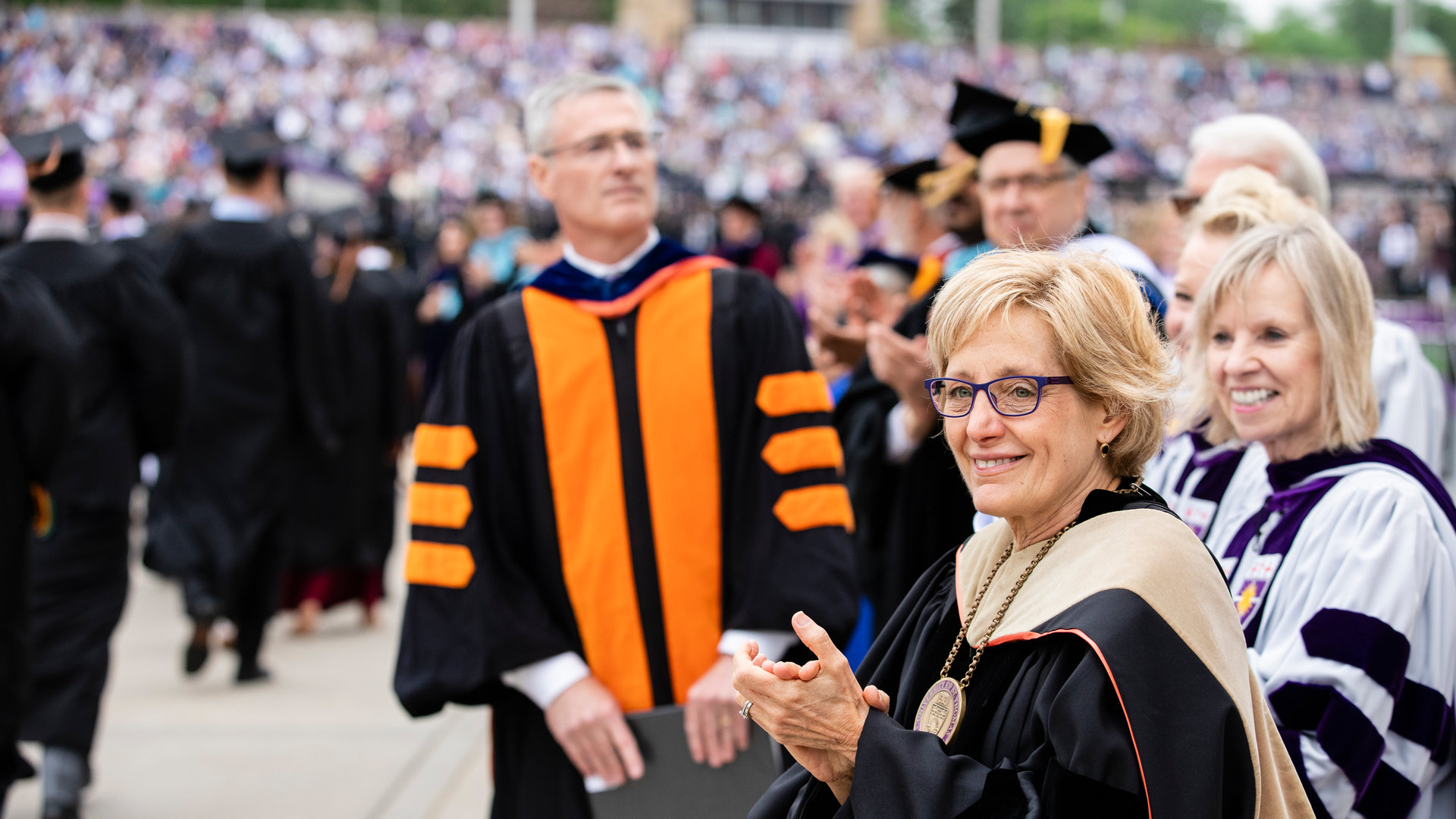 Julie Sullivan and other trustees clap for graduates at a commencement ceremony