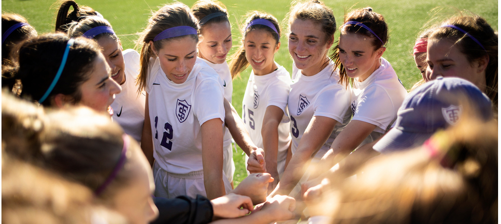 The women's soccer team works together toward a win.