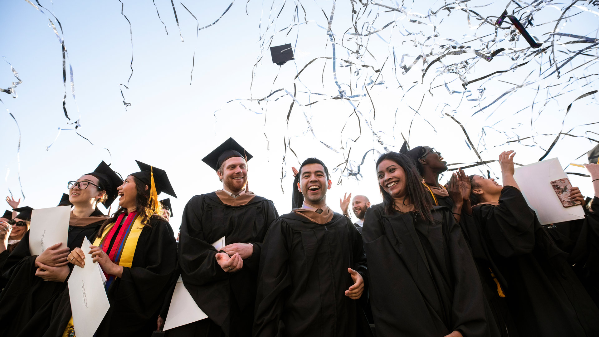 students smile underneath the confetti during graduation