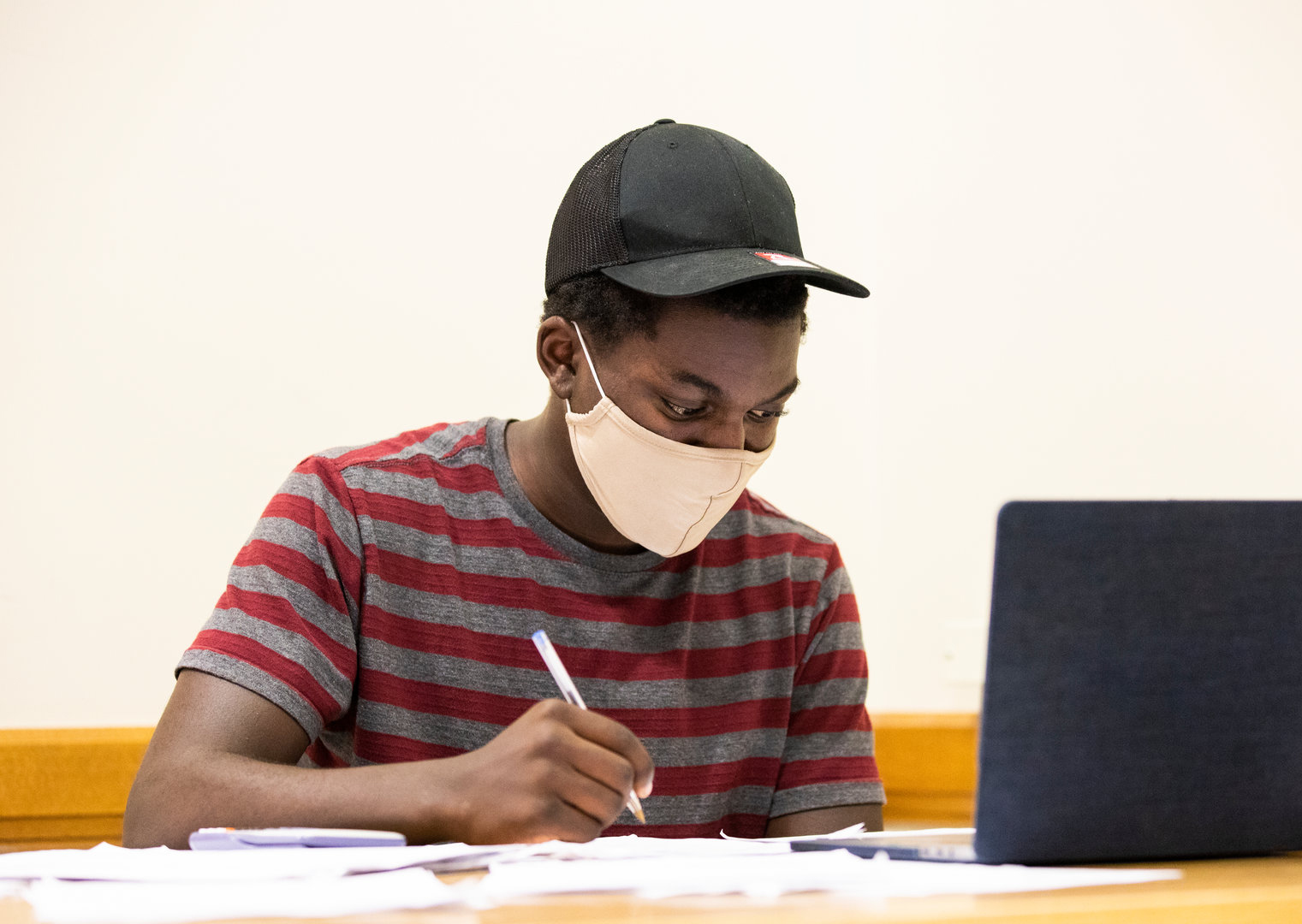 a student studies in the library while wearing a facemask during COVID-19
