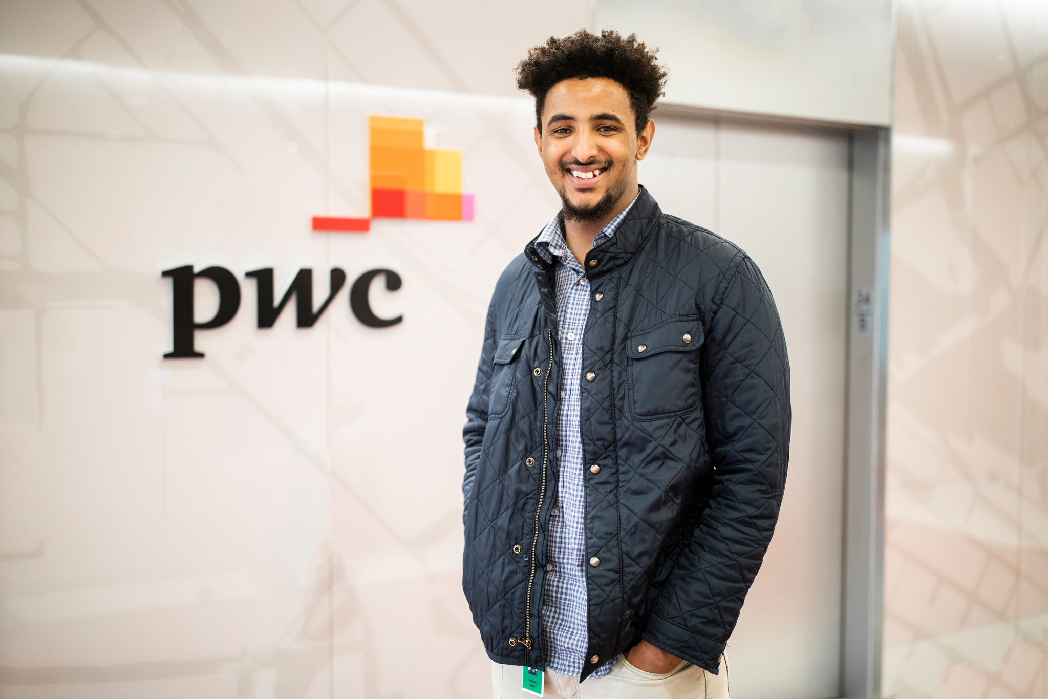 a DFC student poses for a picture at a price-waterhouse-cooper office