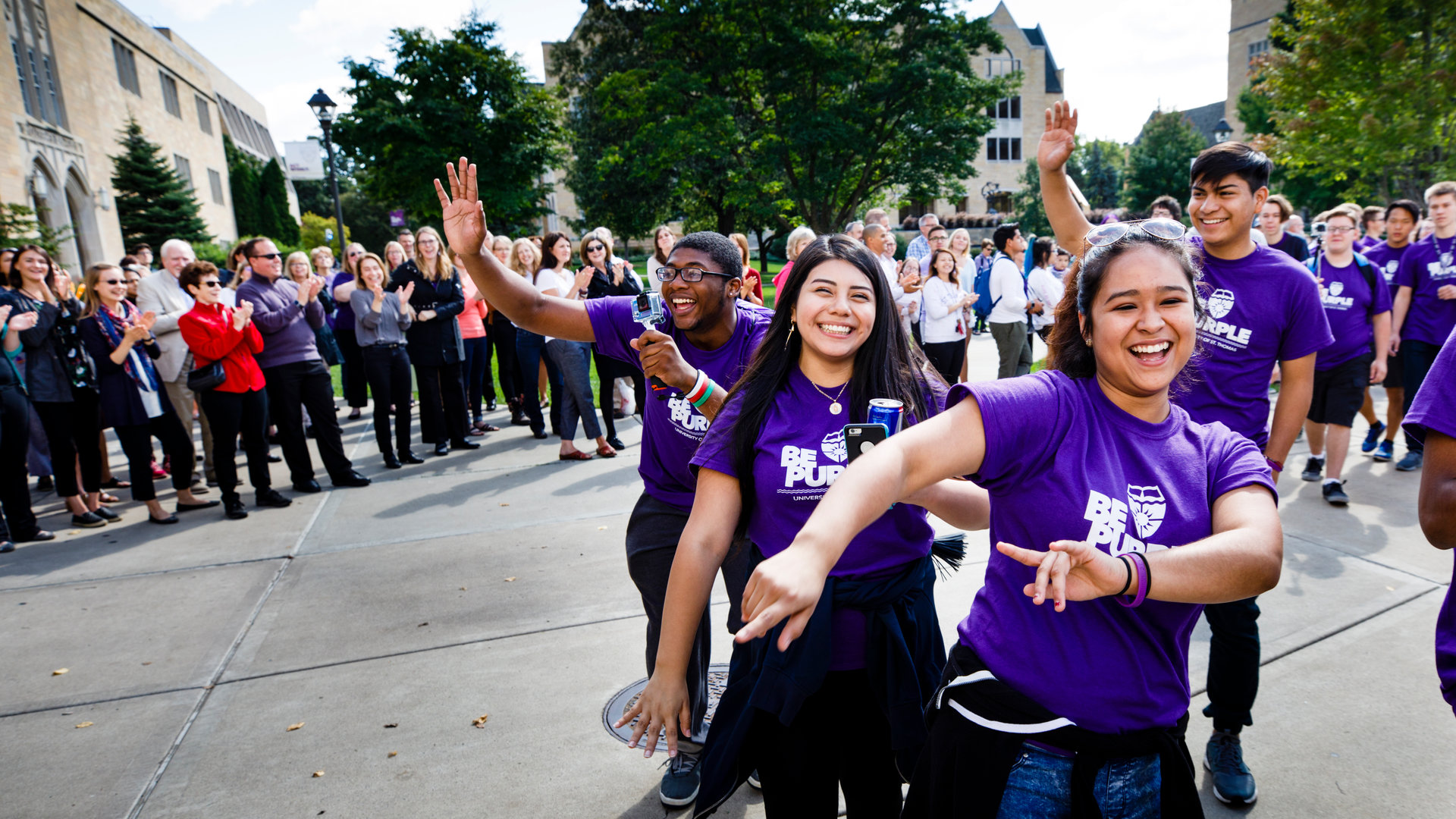 Students march thorugh the arches as part of their freshman experience