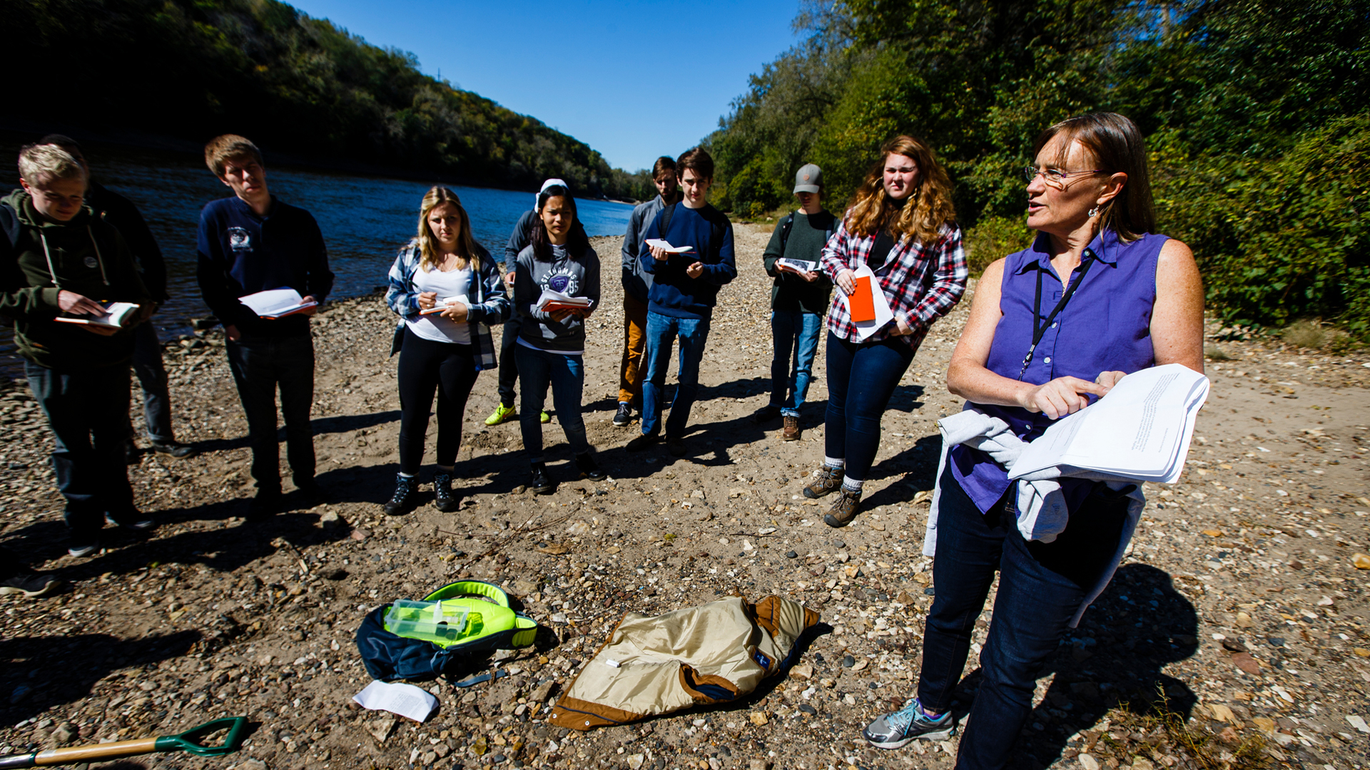 geography professor and students gather near the Mississippi River