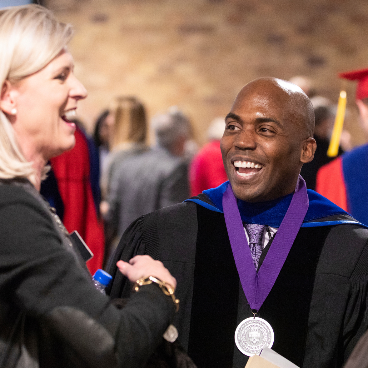 Dean Williams smiles while greeting someone at a graduation ceremony