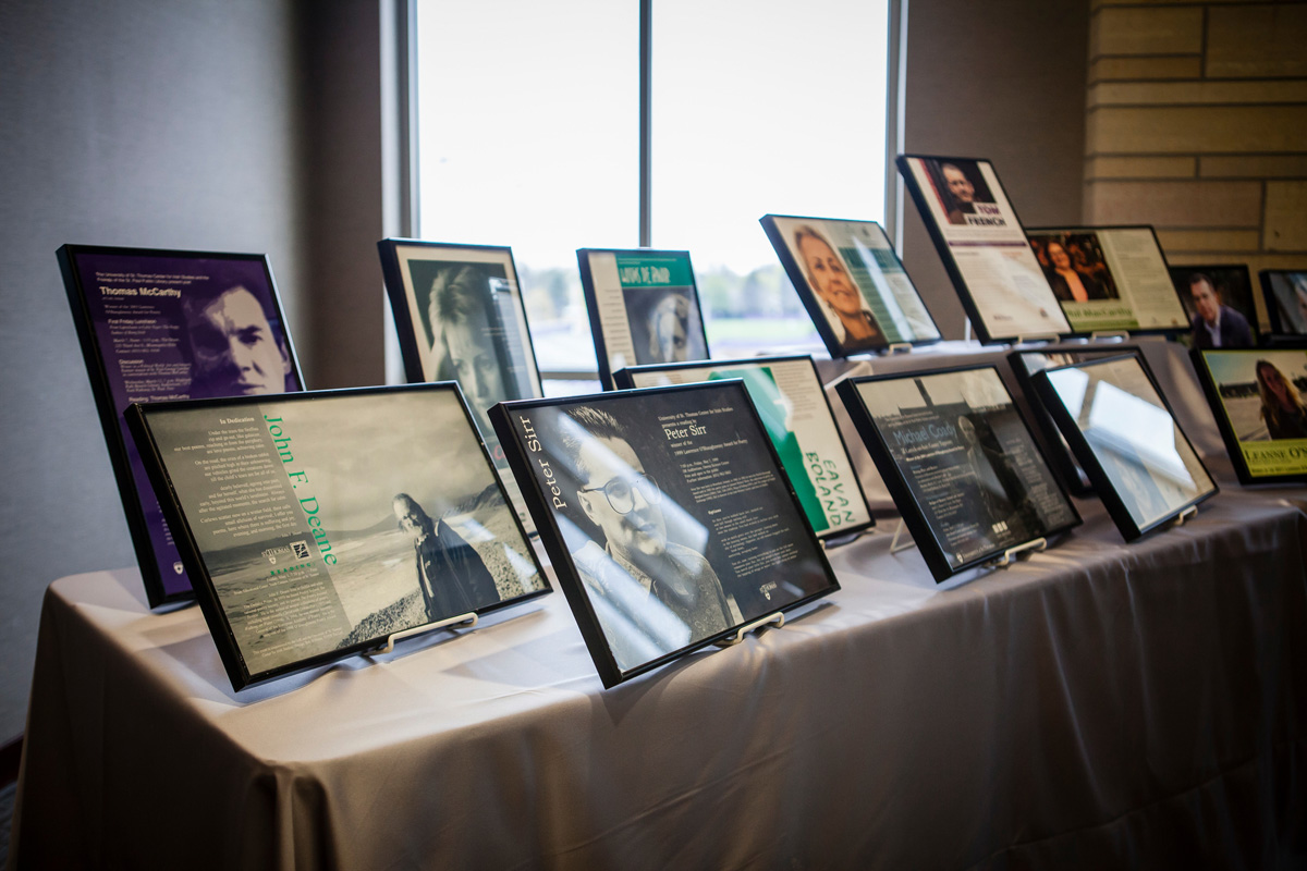 A table filled with pictures of past O'Shaughnessy Poetry Award winners