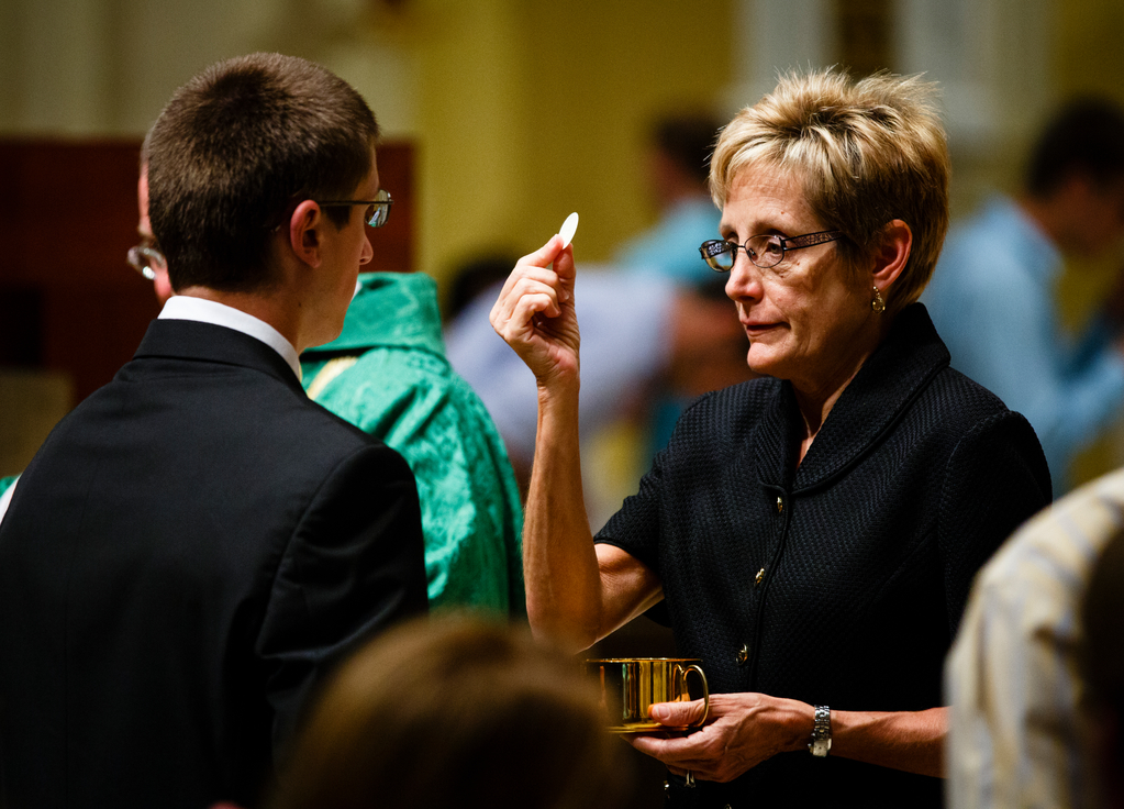 President Sullivan distributes communion at Mass in the Chapel of St. Thomas Aquinas