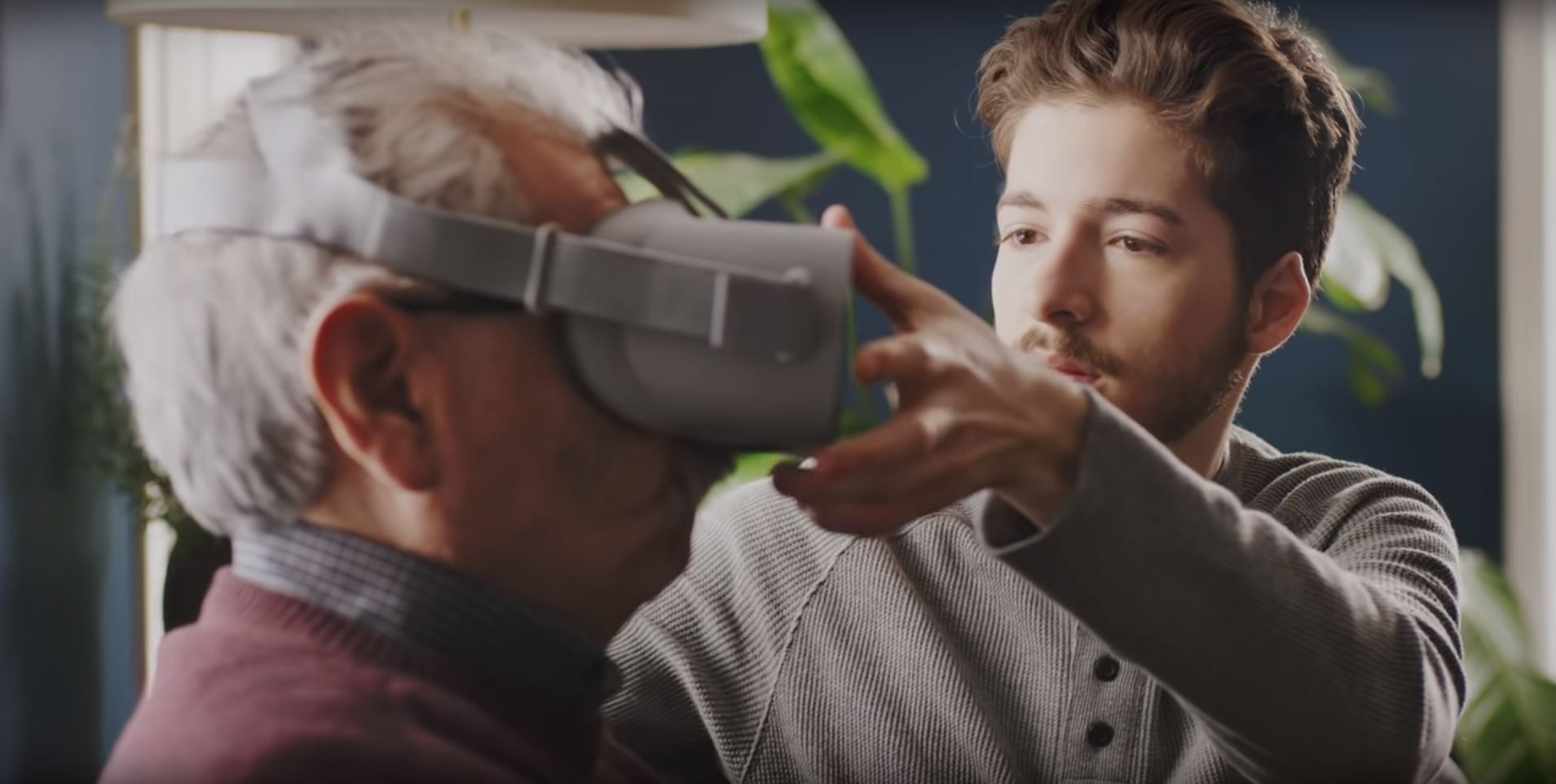 student Enzo Vinholi places a virtual reality headset on an alzheimers patient