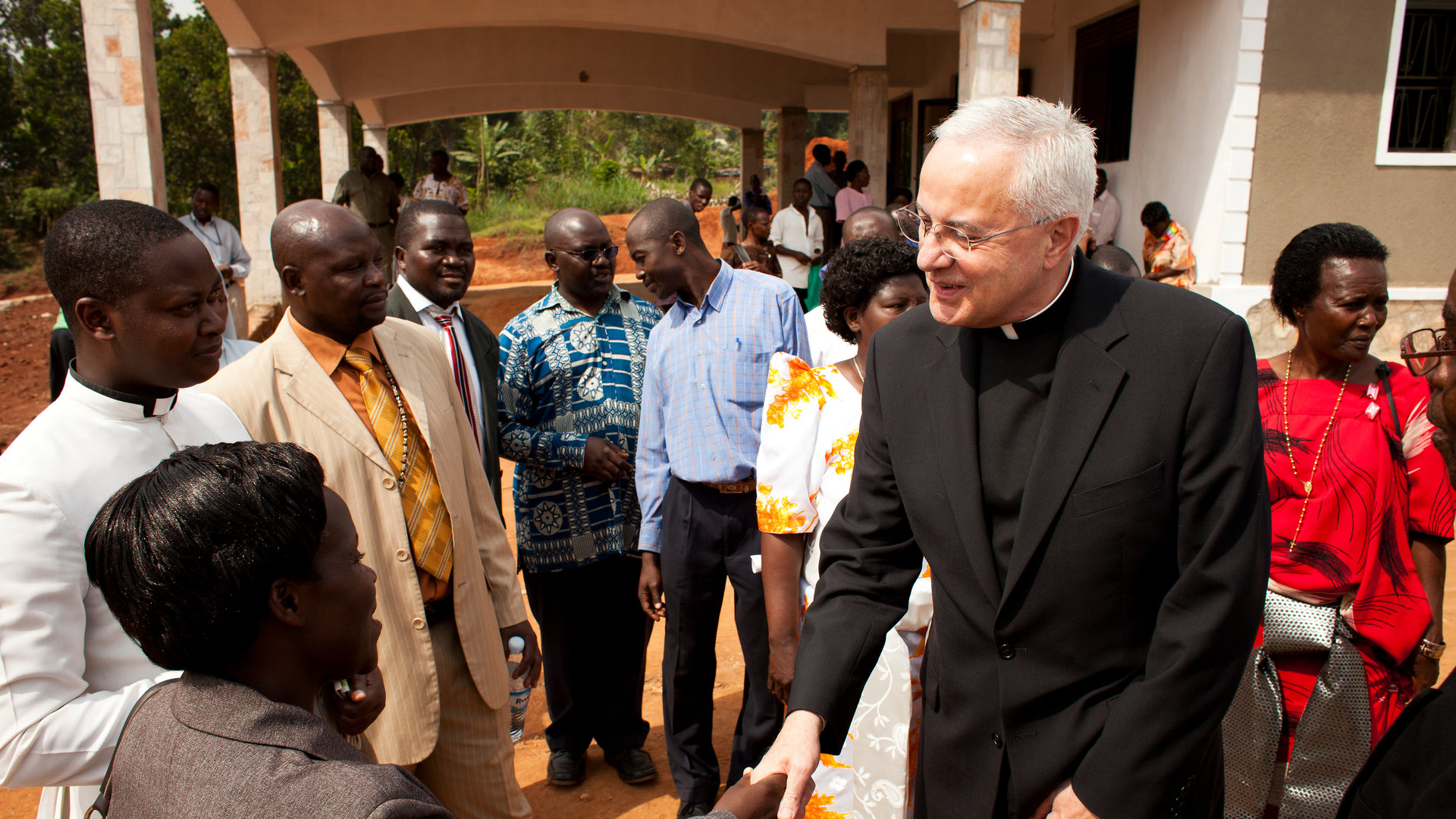 father Dennis Dease shakes hands with locals in Uganda